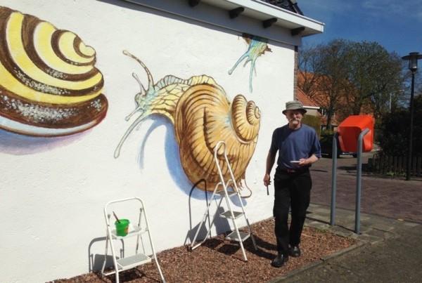 Kunstenaar Frâns Faber druk bezig met zijn muurschildering van de Slakken